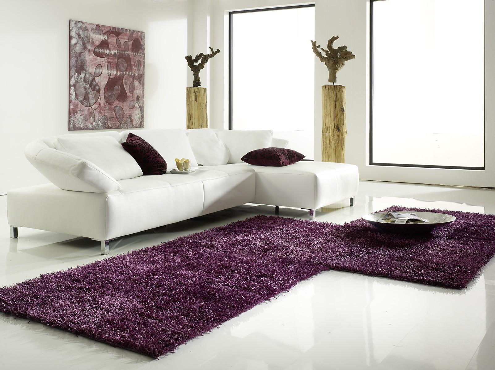 Teppich Al Mano Beispiel: grosse L-Form in lila mit weißer Möbelsitzgruppe