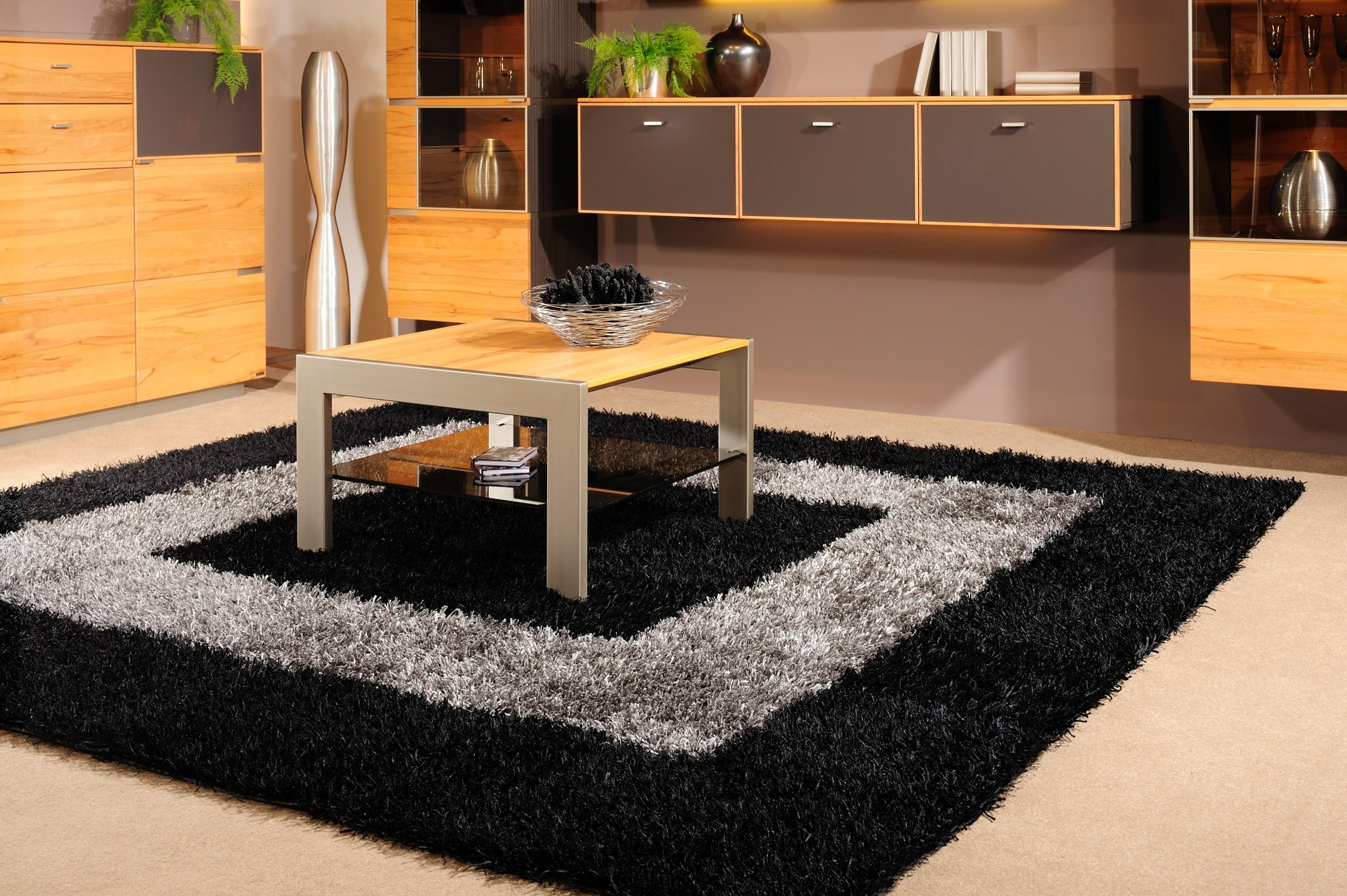 Teppich Al Mano Beispiel: schwarz-graues Muster im Quadrat mit Couchtisch aus Holz